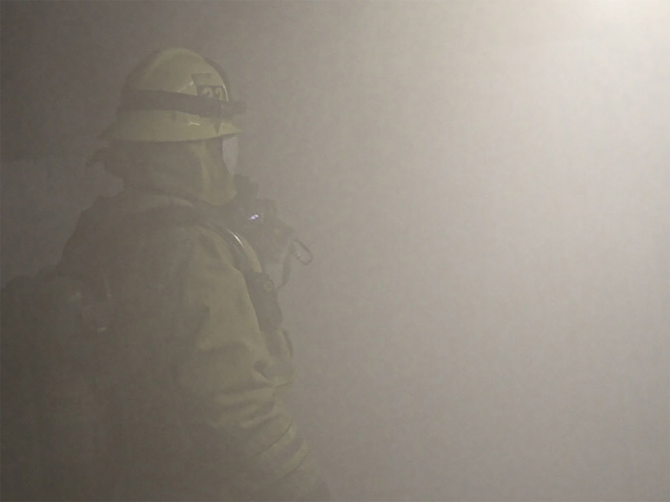 A firefighter stands in smoke