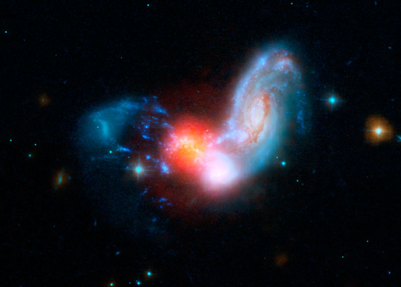 As each slider bar is manipulated, the view transitions from visible light to infrared light. In visible light: The merging galaxies are furiously forming stars inside a dark cocoon of dust. In infrared light: Including infrared light (in red) dramatically reveals where stars are forming.